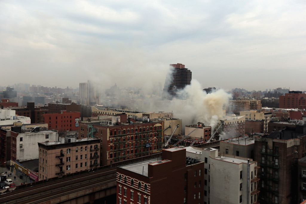 Description of . Smoke rises from a five-alarm fire and building collapse at 1646 Park Ave in the Harlem neighborhood of Manhattan March 12, 2014 in New York City.   (Photo by Justin Heiman/Getty Images)