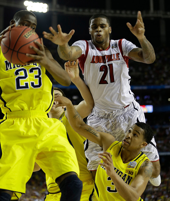 Description of . Louisville forward Chane Behanan (21) Michigan guard Trey Burke (3) and Michigan guard Caris LeVert (23) defend during the second half of the NCAA Final Four tournament college basketball championship game Monday, April 8, 2013, in Atlanta. (AP Photo/David J. Phillip)