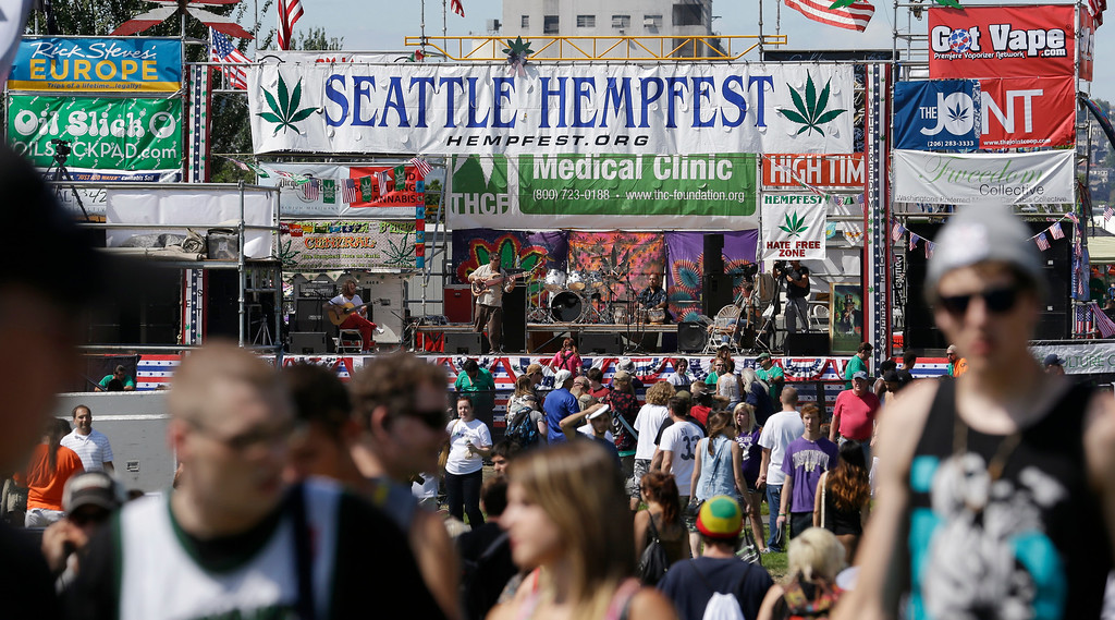 . People walk past the main stage at the first day of Hempfest, Friday, Aug. 16, 2013, in Seattle. Thousands packed the Seattle waterfront park for the opening of a three-day marijuana festival � an event that is part party, part protest and part victory celebration after the legalization of pot in Washington and Colorado last fall. Hempfest was expected to draw as many as 85,000 people per day. (AP Photo/Elaine Thompson)