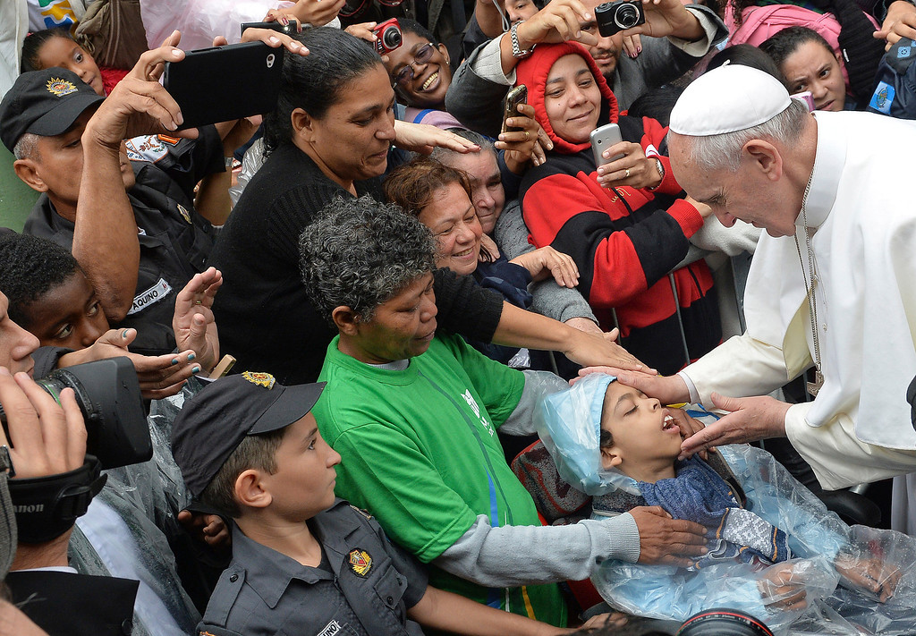 Description of . Pope Francis blesses a child during his visit to the Varginha slum in Rio de Janeiro, Brazil, Thursday, July 25, 2013. Francis on Thursday visited one of Rio de Janeiro's shantytowns, or favelas, a place that saw such rough violence in the past that it's known by locals as the Gaza Strip. (AP Photo/Luca Zennaro, Pool)