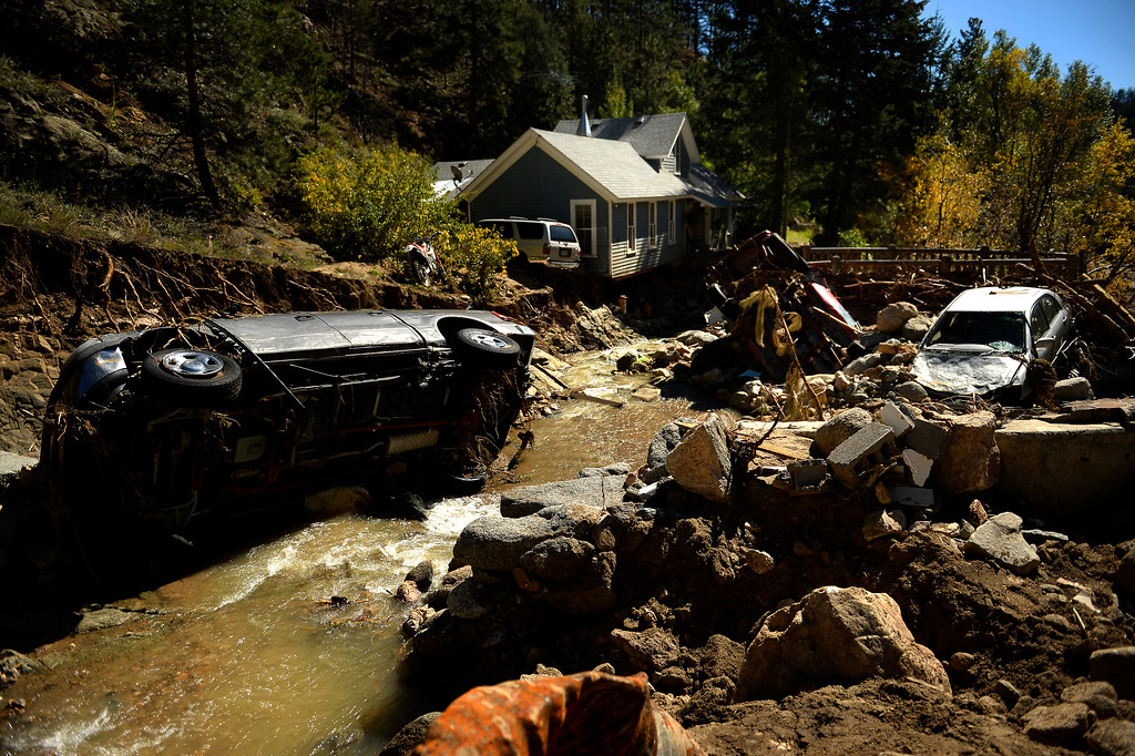 Description of . SALINA, CO. - September 26: Flood damage is still prevalent through Salina as cars lie in the creek and much of the ground is washed from under the front of the home of Matt Smart in Four Mile Canyon on September 26, 2013 Salina, Colo. (Photo By Joe Amon/The Denver Post)