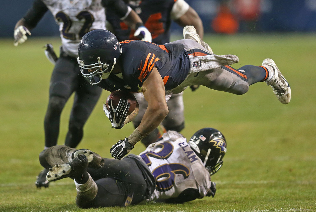 Description of . Matt Forte #22 of the Chicago Bears flies after being hit by Matt Elam #26 of the Baltimore Ravens on a first down run at Soldier Field on November 17, 2013 in Chicago, Illinois. The Bears defeated the Ravens 23-20 in overtime.  (Photo by Jonathan Daniel/Getty Images)
