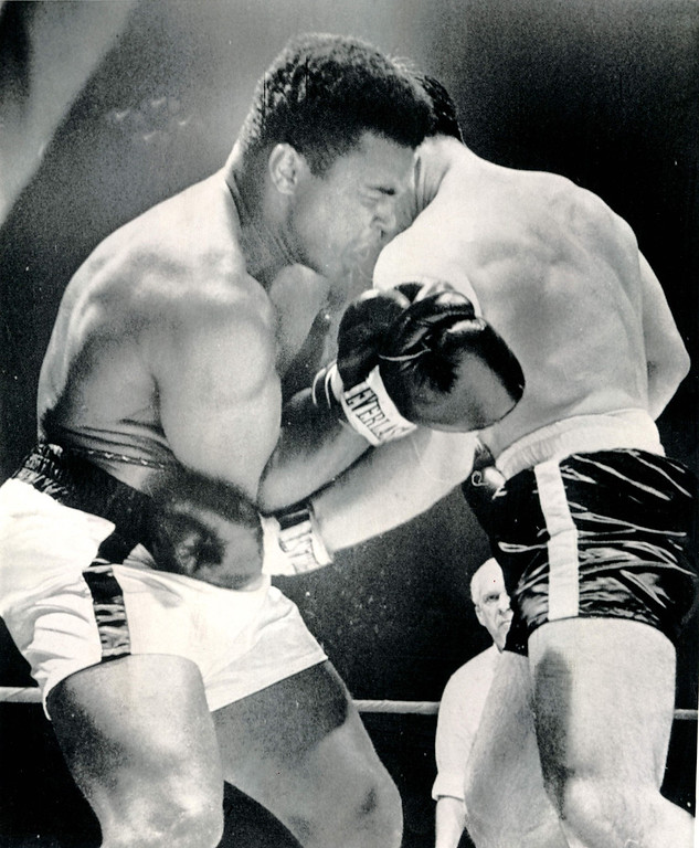 Description of . Cassius Clay (left) grimaces as he takes a left to the body from Canada's George Chuvalo midway in their 15-round bout in Toronto Tuesday night.  Clay boasted later that this proved he could take a body punch.  Clay won a unanimous decision. 1966. Credit: AP