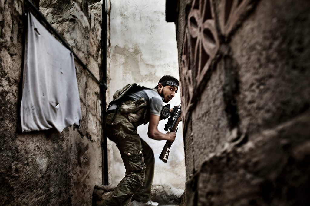 Description of . World Press Photo 2nd prize Spot News Stories by Fabio Bucciarelli, Italy, for Agence France-Presse, a Free Syrian Army (FSA) fighter takes position during the clashes against Syrian government forces in Sulemain Halabi district in Aleppo, Syria, Oct. 10, 2012. (AP Photo/Fabio Bucciarelli, Agence France-Presse)