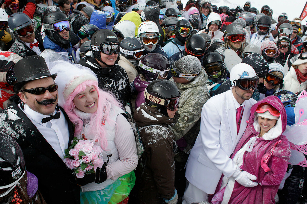 Description of . Eighty-eight couples gather in a blizzard atop a mountain to get married or renew their vows, at the 22nd Annual Marry Me & Ski Free Mountaintop Matrimony, at Loveland Ski Area, in Colorado, Thursday, Feb. 14, 2013. At left are couple Joseph and Elizabeth Antonio, who renewed their vows after six years of marriage, and at right are newlyweds Mary Stipe and Ryan Kargol. (AP Photo/Brennan Linsley)