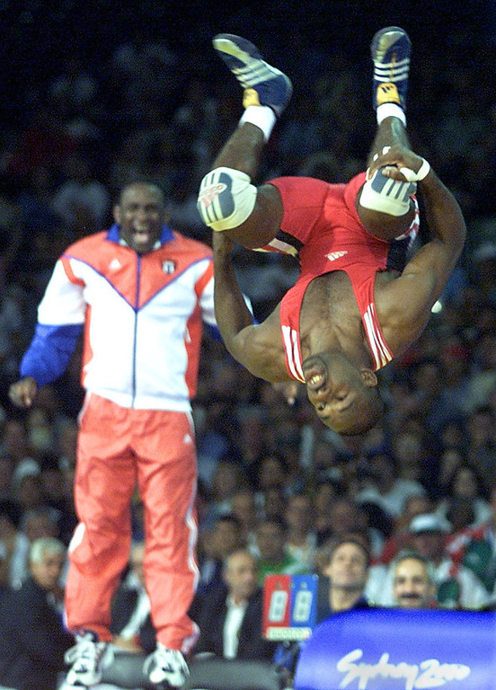 Description of . Filiberto Azcuy of Cuba celebrates his gold medal victory over Japan's Katsuhiko Nagata in the men's 69kg Greco-Roman wrestling final at the XXVII Olympic Summer Games 27 September 2000 in Sydney. ANTONIO SCORZA/AFP/Getty Images