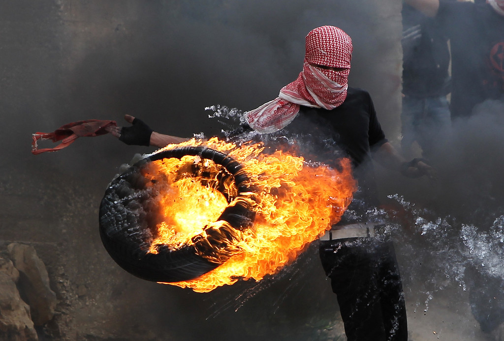 Description of . A Palestinian sets fire to a tire during clashes between hundreds of Palestinians and Israeli soldiers outside the Ofer prison following a march marking the 65th Nakba day or