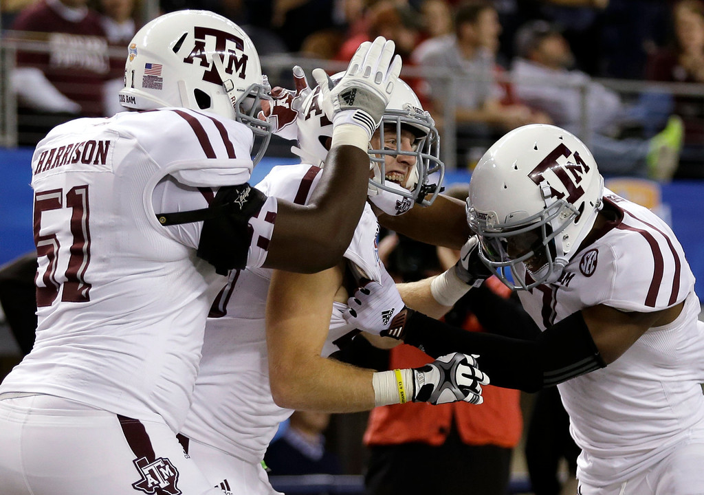 Description of . Texas A&M's Jarvis Harrison (51) and Uzoma Nwachukwu, right, celebrate with Ryan Swope, center, following his touchdown in the second half of the Cotton Bowl NCAA college football game against Oklahoma on Friday, Jan. 4, 2013, in Arlington, Texas. (AP Photo/LM Otero)