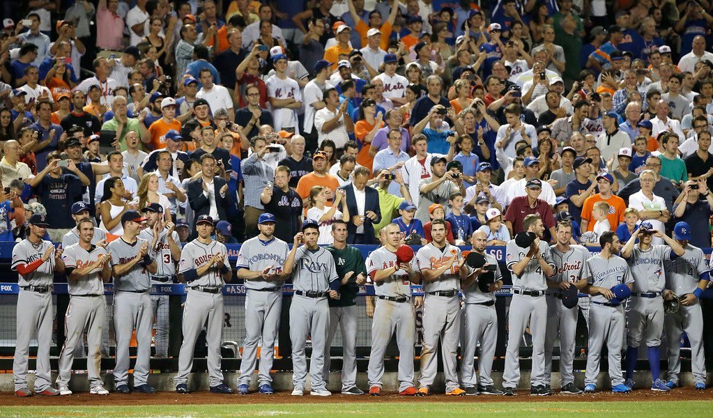 Description of . American League players applaud as Mariano Rivera, of the New York Yankees,  takes to the mound during the eighth inning of the MLB All-Star baseball game, on Tuesday, July 16, 2013, in New York.  (AP Photo/Matt Slocum)