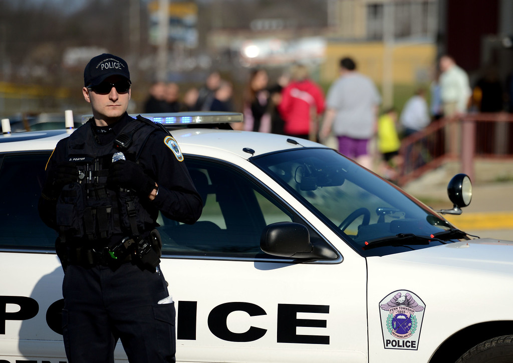 Description of . A police officer guards the entrance Heritage Elementary School as students are dismissed after more than a dozen students were stabbed by a knife wielding suspect at nearby Franklin Regional High School on Wednesday, April 9, 2014, in Murrysville, Pa., near Pittsburgh. The suspect, a male student, was taken into custody and is being questioned. (AP Photo/Tribune Review, Sean Stipp)