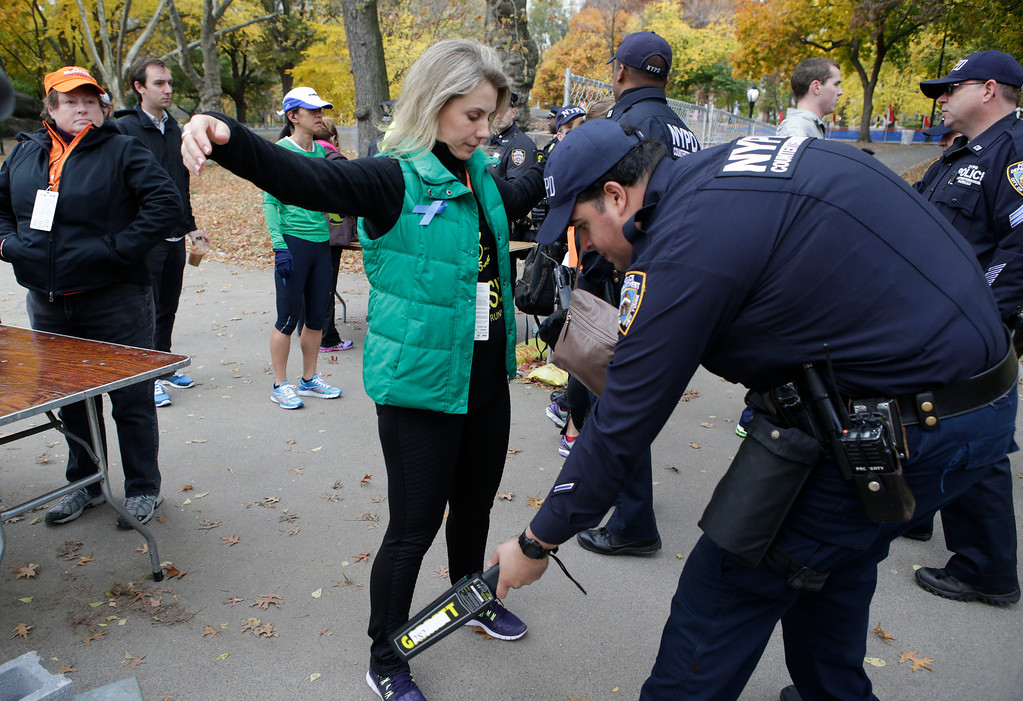 Description of . A counterterrorism police officer uses a metal detecting wand at a security checkpoint near the finish line of the 2013 New York City marathon, Sunday, Nov. 3, 2013, in New York. Increased security is visible in the wake of the Boston Marathon bombings. (AP Photo/Kathy Willens)