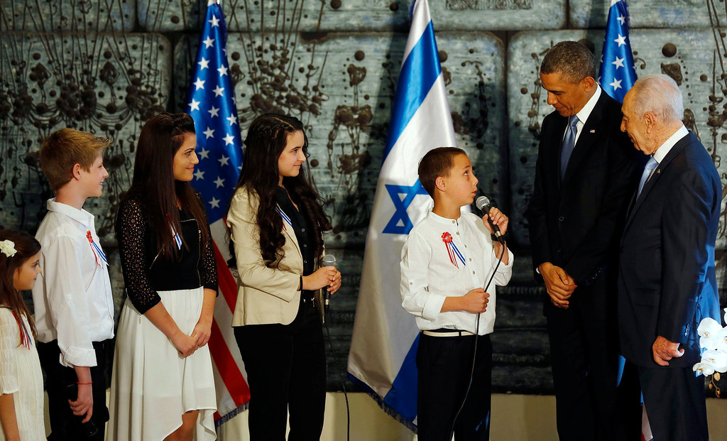 Description of . U.S. President Barack Obama (2nd R) and Israel's President Shimon Peres (R) listen to 13-year old Daniel Pruzansky sing after Obama signed the guest book in Jerusalem, March 20, 2013.    REUTERS/Larry Downing