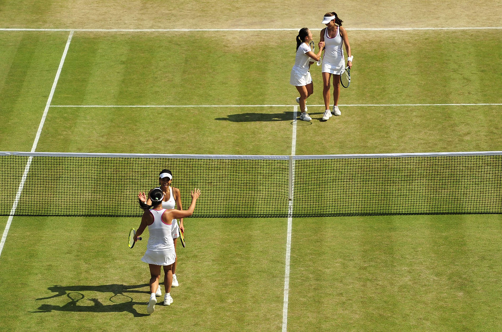 Description of . Japan\'s Shuko Aoyama (2nd R) and South Africa\'s Chanelle Scheepers (R) play against China\'s Peng Shuai and Taiwan\'s Hsieh Su-Wei during their ladies doubles semi-final match on day eleven of the 2013 Wimbledon Championships tennis tournament at the All England Club in Wimbledon, southwest London, on July 5, 2013. GLYN KIRK/AFP/Getty Images