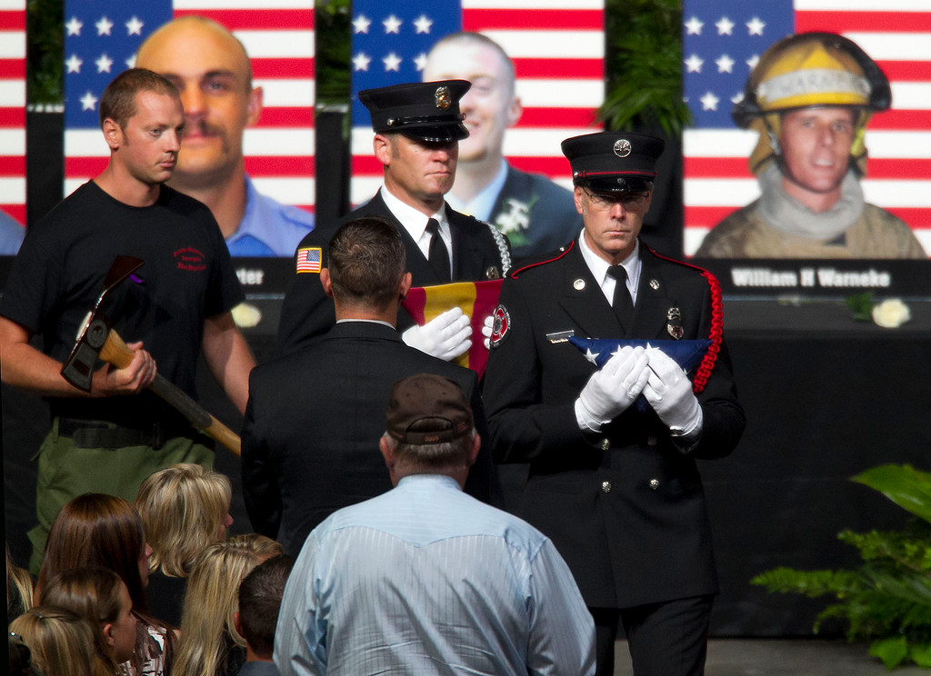 Description of . Firefighters present American flags, Arizona flags and Pulaskis to family members of the fallen firefighters during a memorial service for the 19 fallen firefighters at Tim's Toyota Center in Prescott Valley, Ariz. on Tuesday, July 9, 2013.   (AP Photo/The Arizona Republic, Michael Chow, Pool)