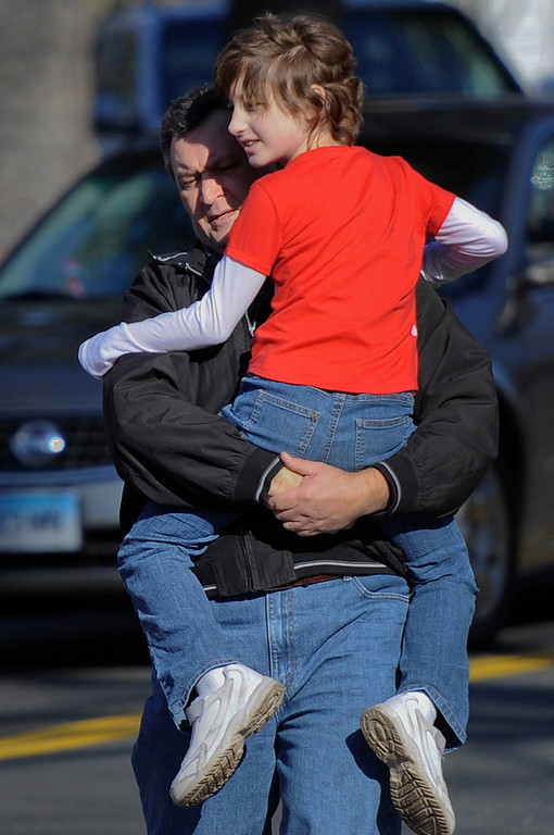 Description of . A man carries a child away from the area of a shooting at the Sandy Hook Elementary School in Newtown, Conn., about 60 miles (96 kilometers) northeast of New York City, Friday, Dec. 14, 2012.  A man opened fire Friday inside two classrooms at the school where his mother worked as a teacher, killing 26 people, including 20 children.  The killer, armed with two handguns, committed suicide at the school and another person was found dead at a second scene, bringing the toll to 28, authorities said. A law enforcement official identified the gunman as 20-year-old Adam Lanza.  (AP Photo/Jessica Hill)