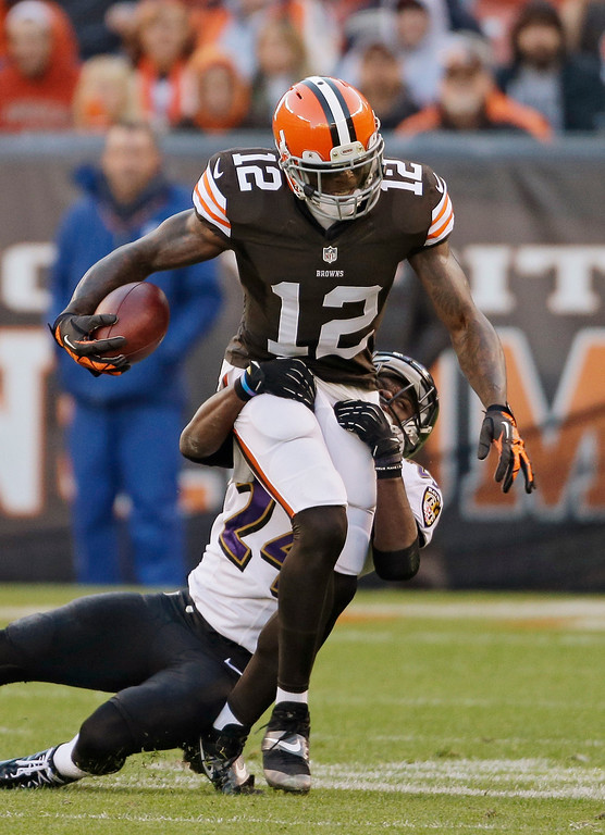 . Cleveland Browns wide receiver Josh Gordon (12) is tackled short of a first down by Baltimore Ravens cornerback Corey Graham in the first quarter of an NFL football game Sunday, Nov. 3, 2013, in Cleveland. (AP Photo/Mark Duncan)