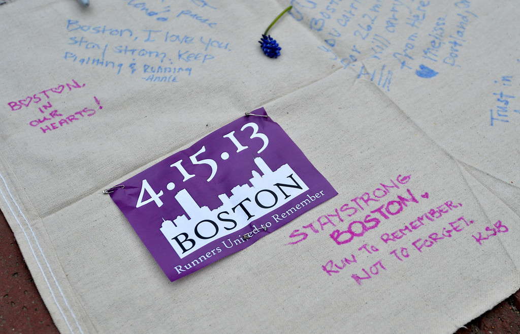 """Description of . Messages on a banner are seen during a vigil on the Boston Common on April 16, 2013 in Boston, in the aftermath of two explosions that struck near the finish line of the Boston Marathon on April 15. Investigators said the range of suspects and motives in the grisly Boston bombings remained \""""wide open\"""" as experts assessed remnants of the crude devices designed to inflict maximum suffering.    STAN HONDA/AFP/Getty Images"""