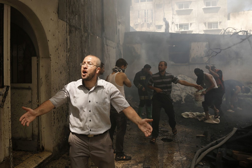 Description of . Palestinians try to put out a building on fire following several Israeli strikes on Gaza City on July 30, 2014. So far, according to Palestinian medics, 1,283 people have been killed and more than 7,170 wounded since the start of the Israeli offensive, which began with an intensive air campaign on July 8 and expanded when Israel sent ground troops into the Gaza periphery on July 17. AFP PHOTO / MOHAMMED ABED/AFP/Getty Images