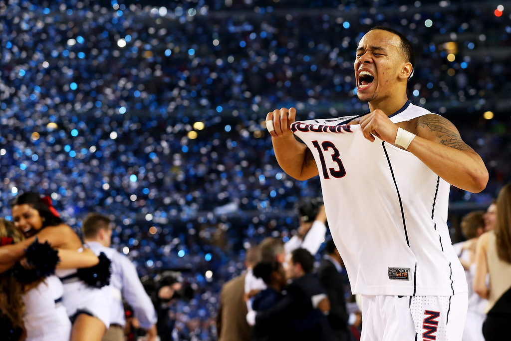 Description of . ARLINGTON, TX - APRIL 07:  Shabazz Napier #13 of the Connecticut Huskies celebrates on the court after defeating the Kentucky Wildcats 60-54 in the NCAA Men\'s Final Four Championship at AT&T Stadium on April 7, 2014 in Arlington, Texas.  (Photo by Ronald Martinez/Getty Images)