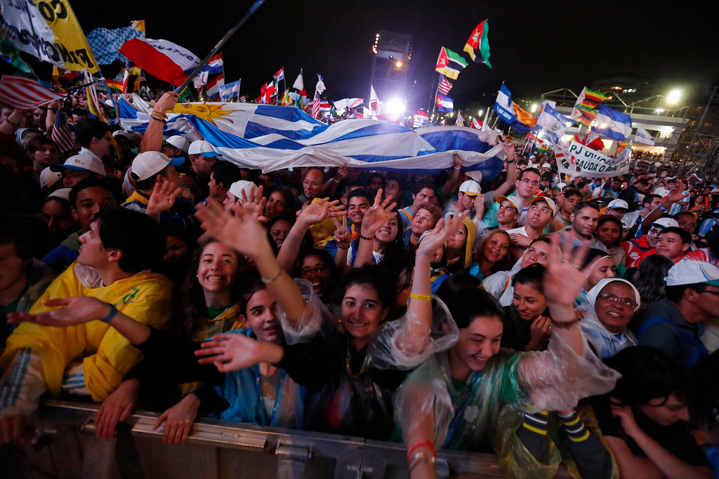 Description of . Thousands of young pilgrims get revved up as they gather on Copacabana Beach for a World Youth Day inaugural Mass in Rio de Janeiro, Brazil, Tuesday, July 23, 2013. A cold rain Tuesday night didn't stop upward of 500,000 faithful from gathering on to mark the event. (AP Photo/Jorge Saenz)