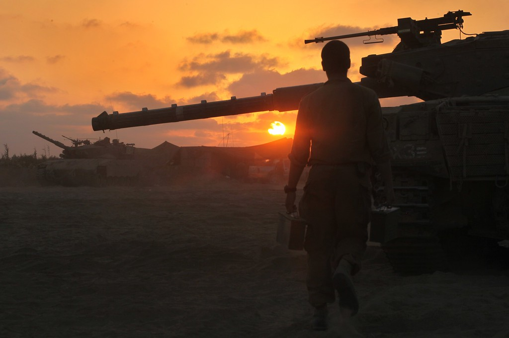 Description of . An Israeli soldier walks past a Merkava tank along the border between Israel and the Hamas-controlled Gaza Strip, on July 30, 2014, after returning from combat in the Palestinian enclave. At least 17 people were killed in an Israeli strike on a packed Gaza market in a deadly raid that came as Israel was observing a four-hour humanitarian lull. AFP PHOTO/GIL  COHEN MAGEN/AFP/Getty Images