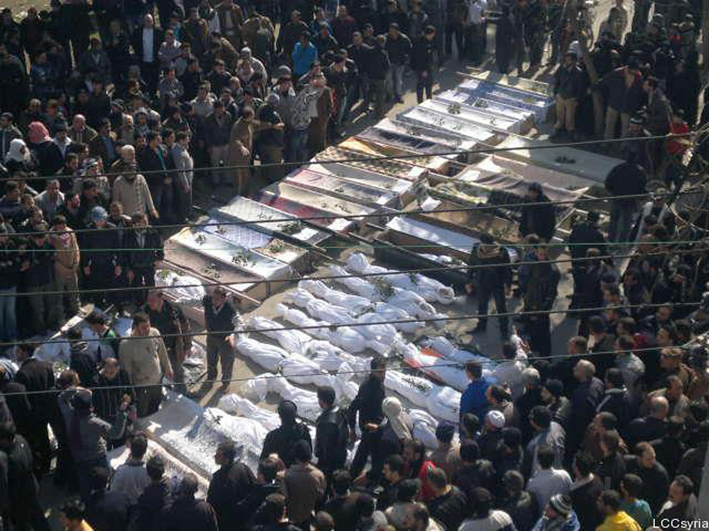 Description of . In this citizen journalism image provided by the Local Coordination Committees in Syria, Syrian mourners gather around the coffins of the victims who were killed early Saturday by the bombardment of mortars and rockets during a mass funeral procession, in Khaldiyeh neighborhood in Homs province, central Syria, on Saturday Feb. 4, 2012. Russia and China vetoed a U.N. Security Council resolution backing calls for Syrian President Bashar Assad to step down, despite international outrage Saturday over a devastating bombardment of the city of Homs by his regime's forces. Activists said more than 200 were killed in the bloodiest episode of the nearly 11-month uprising. (AP Photo/Local Coordination Committees in Syria)