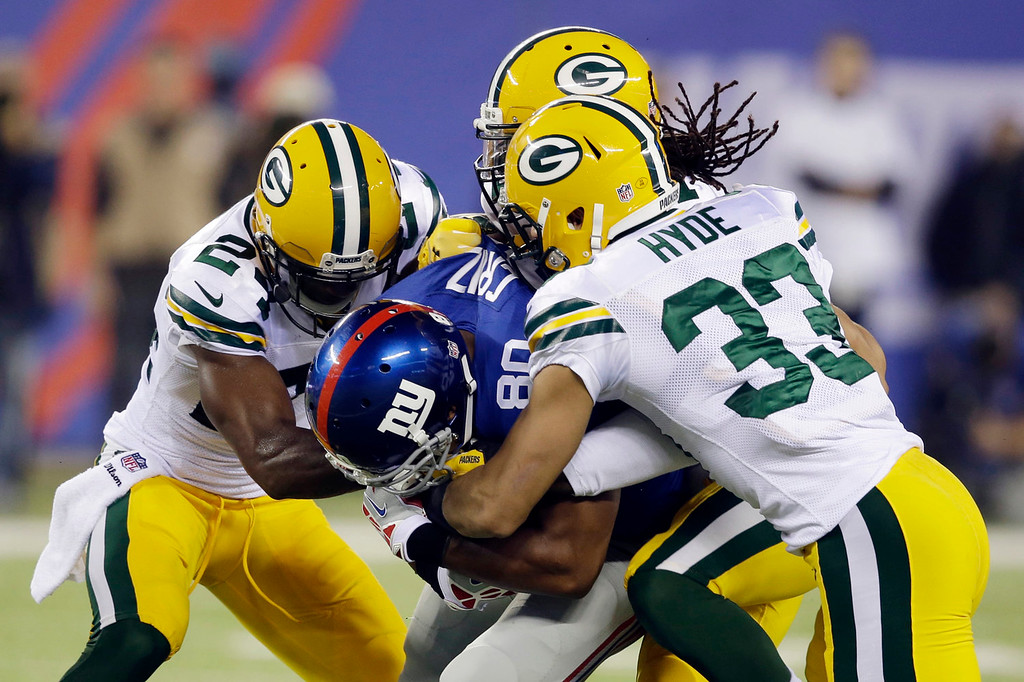 Description of . New York Giants wide receiver Victor Cruz (80) is tackled by Micah Hyde (33), Davon House, and Jarrett Bush, left, during the first half of an NFL football game Sunday, Nov. 17, 2013, in East Rutherford, N.J.  (AP Photo/Seth Wenig)