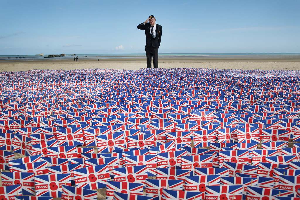 Description of . WW2 veteran Fred Holborn, from the Fleet Air Arm, salutes as he looks at British Legion Union flags carrying thank you messages planted in the sand on Gold beach on June 5, 2014 near Asnelles, France. 20,000 paper flags are being planted. Each one carries a personal message of Remembrance submitted by Royal British Legion supporters.  (Photo by Peter Macdiarmid/Getty Images)