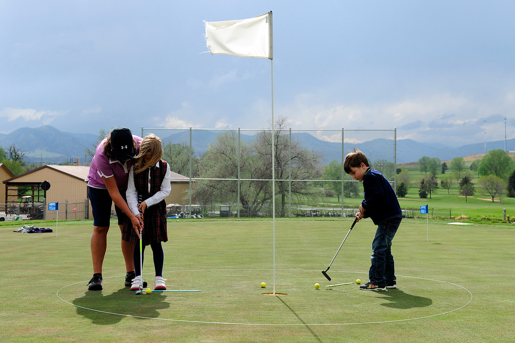 Description of . DENVER, CO - MAY 7: Nina Krats, left, helps Eva Hellvig, 7, with putting practice, while Cameron Fay, 6, right, works on his own during class at Foothills Golf Course on May 7, 2014, in Denver, Colorado. Foothills Park and Recreation is aiming to increase participation in its golf programs, especially in regards to youth involvement. (Photo by Anya Semenoff/The Denver Post)