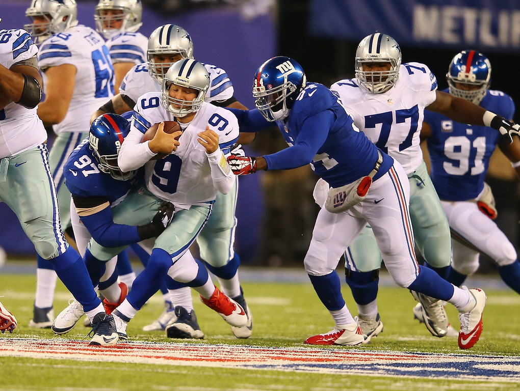 Description of . Tony Romo #9 of the Dallas Cowboys is sacked by  Linval Joseph #97 and  Spencer Paysinger #54 of the New York Giants during their game at MetLife Stadium on November 24, 2013 in East Rutherford, New Jersey.  (Photo by Al Bello/Getty Images)