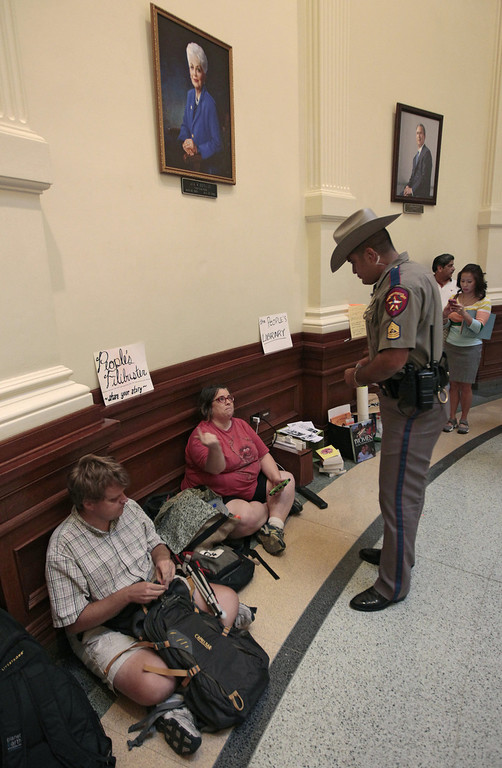 Description of . A Department of Public Safety officer asks Lainie Duro of Occupy Austin to move her
