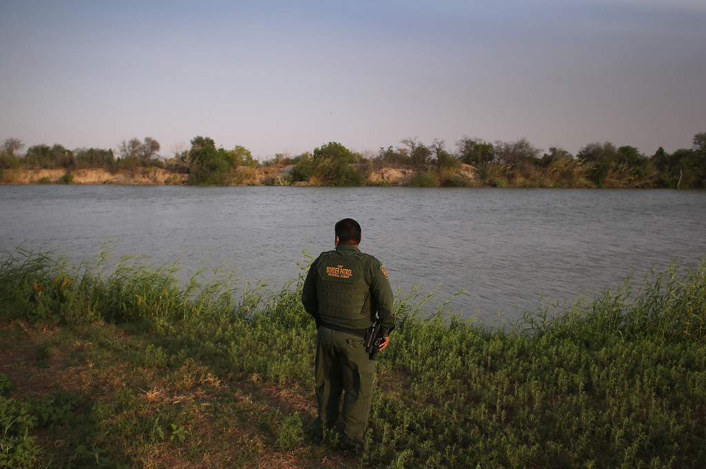 Description of . MCALLEN, TX - APRIL 10:  U.S. Border Patrol agent Sal De Leon looks across the Rio Grande River into Mexico at the U.S.-Mexico border while on patrol on April 10, 2013 in McAllen, Texas. According to the Border Patrol, undocumented immigrant crossings have increased more than 50 percent in Texas\' Rio Grande Valley sector in the last year. Border Patrol agents say they have also seen an additional surge in immigrant traffic since immigration reform negotiations began this year in Washington D.C. Proposed refoms could provide a path to citizenship for many of the estimated 11 million undocumented workers living in the United States.  (Photo by John Moore/Getty Images)