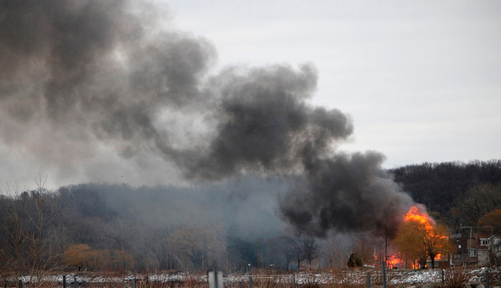 Description of . Homes burn on Lake Road where two Webster firefighters were killed and two others were wounded after a gunman opened fire at a blaze in Webster, New York, December 24, 2012. A gunman shot dead two volunteer firefighters and injured two others when he ambushed them at the scene of an early morning house fire in a suburb of Rochester, New York, authorities said on Monday.   REUTERS/Max Schulte/Democrat and Chronicle/Handout