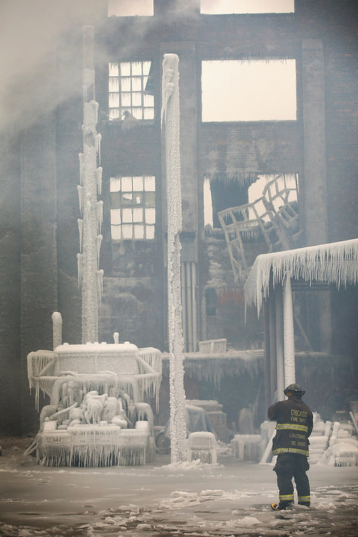 Description of . Firefighters help to extinguish a massive blaze at a vacant warehouse on January 23, 2013 in Chicago, Illinois. More than 200 firefighters battled a five-alarm fire as temperatures were in the single digits. (Photo by Scott Olson/Getty Images)