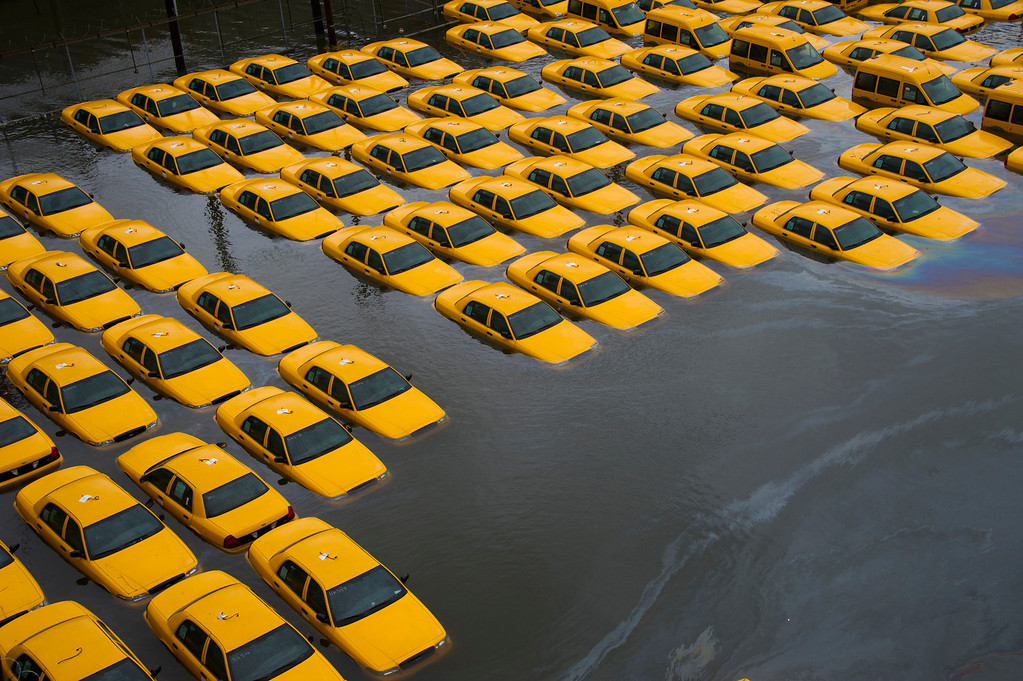 Description of . In this Oct. 30, 2012 file photo, a parking lot full of yellow cabs in Hoboken, N.J.  is flooded as a result of Superstorm Sandy.  (AP Photo/Charles Sykes, File)