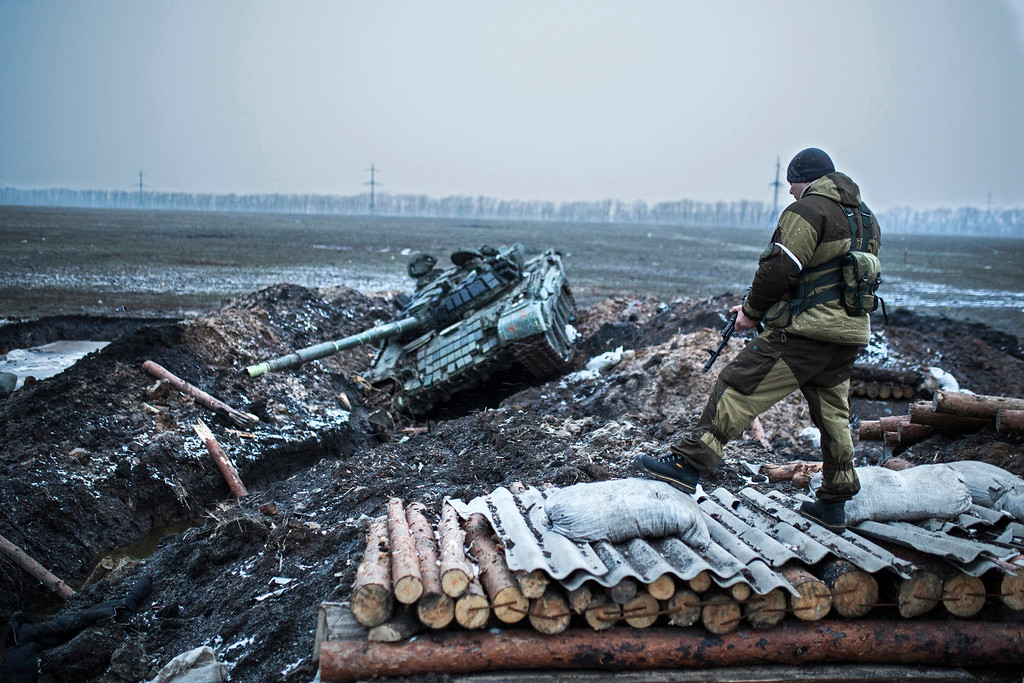 Description of . A pro-Russian rebel guards a captured former Ukrainian Army checkpoint outside Vuhlehirsk, Donetsk region, eastern Ukraine, Thursday, Feb. 5, 2015.  The rebels have closed in around the town in a strategy they triumphantly refer to as the Debaltseve cauldron. Separatists recently burst through government lines in the rural settlement of Vuhlehirsk. (AP Photo/Vadim Braydov)