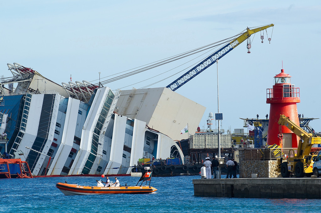 Description of . Engineers at work on the Costa Concordia ahead of the start of the salvage operation on September 16, 2013 in Isola del Giglio, Italy. Work begins today to right the stricken Costa Concordia vessel, which sank on January 12, 2012. If the operation is successful, it will then be towed away and scrapped. The procedure, known as parbuckling, has never been carried out on a vessel as large as Costa Concordia before. (Photo by Marco Secchi/Getty Images)
