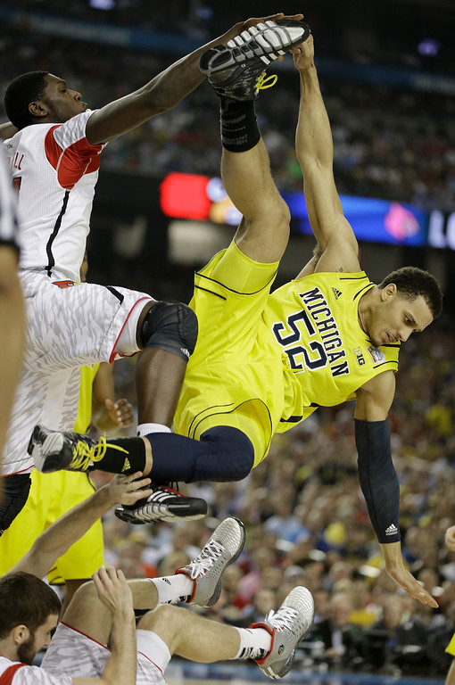 Description of . Michigan forward Jordan Morgan (52) falls to the court against Louisville forward Montrezl Harrell, top left, and Louisville guard/forward Luke Hancock (11) during the second half of the NCAA Final Four tournament college basketball championship game Monday, April 8, 2013, in Atlanta. (AP Photo/Charlie Neibergall)