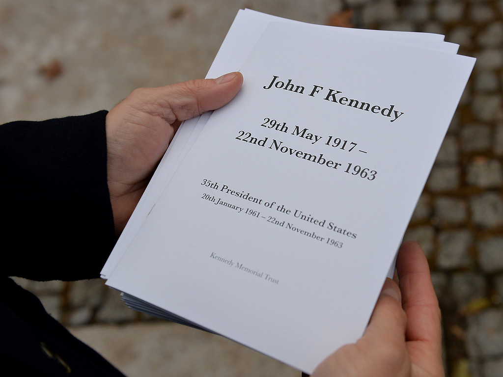Description of . An attendee holds an order of service at a memorial for former US President John F Kennedy in Runnymede, Surrey on November 22, 2013, to mark the 50th anniversary of his assassination. AFP PHOTO / BEN  STANSALL/AFP/Getty Images