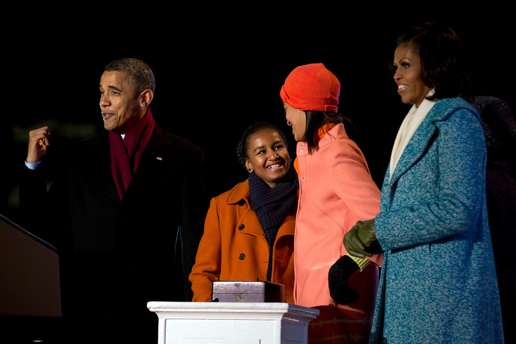 Description of . President Barack Obama, first lady Michelle Obama and their daughters Sasha, second from left, and Malia react as the girls flip the switch to light the National Christmas Tree during the 90th annual National Christmas Tree Lighting on the Ellipse, Thursday, Dec. 6, 2012, in Washington. This year's giant blue spruce is new, transplanted in October on the Ellipse, south of the White House. (AP Photo/Carolyn Kaster)