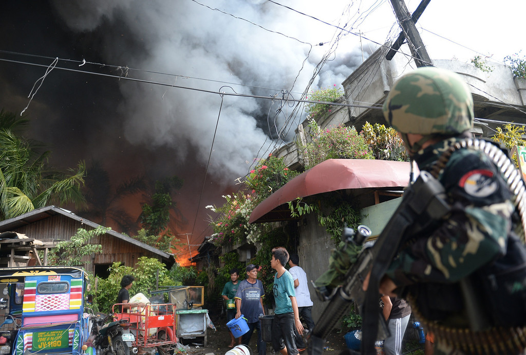 Description of . Philippine soldiers look at enemy positions as they try to protect residents putting out fires in their homes during a fire fight with Muslim rebels in Zamboanga City, in southern island of Mindanao on September 12, 2013.   AFP PHOTO/TED ALJIBE/AFP/Getty Images