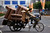 A man rides a tricycle loaded with lounge chairs along a road in Beijing June 5, 2012.    REUTERS/David Gray