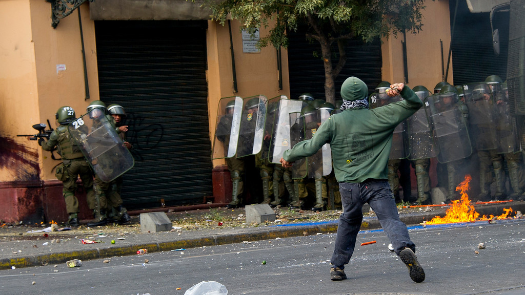 Description of . Students clash with riot police during a protest to demand Chilean President Sebastian Pinera\'s government to improve the public education quality, in Santiago, on April 11,2013. MARTIN BERNETTI/AFP/Getty Images