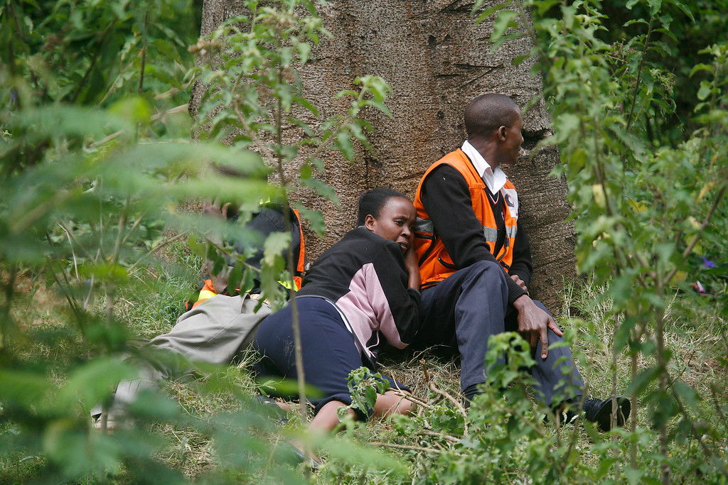 Description of . Medics take cover behind a large tree  as gunfire and explosions are heard from  the Westgate Mall   in Nairobi Kenya Monday Sept. 23 2013. (AP Photo/ Jerome Delay)