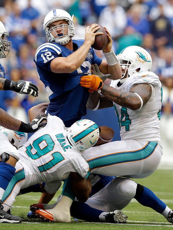 Description of . Indianapolis Colts' Andrew Luck (12) tries to throw the football as he is sacked by Miami Dolphins' Philip Wheeler (52), behind, during the second half an NFL football game Sunday, Sept. 15, 2013, in Indianapolis. (AP Photo/Michael Conroy)
