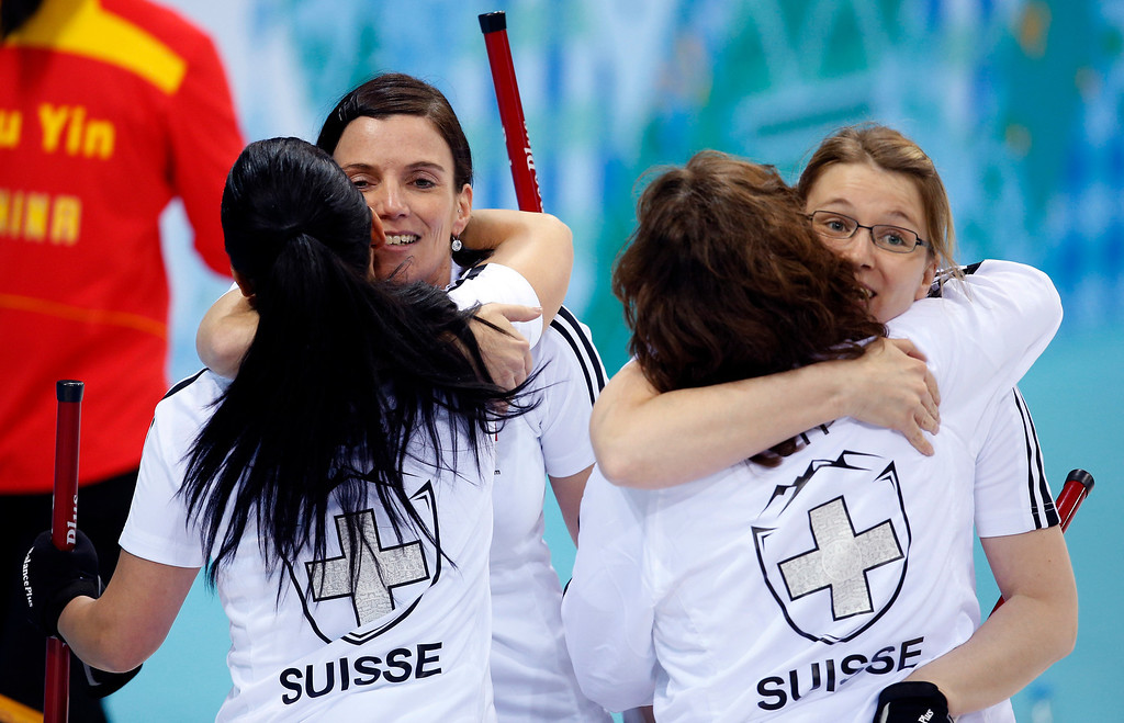 Description of . Switzerlandís Carmen Schaefer, back to camera at left, hugs Carmen Kueng, and Mirjam Ott, back to camera at right, hugs Janine Greiner, after defeating China during women's curling competition at the 2014 Winter Olympics, Monday, Feb. 17, 2014, in Sochi, Russia. (AP Photo/Robert F. Bukaty)