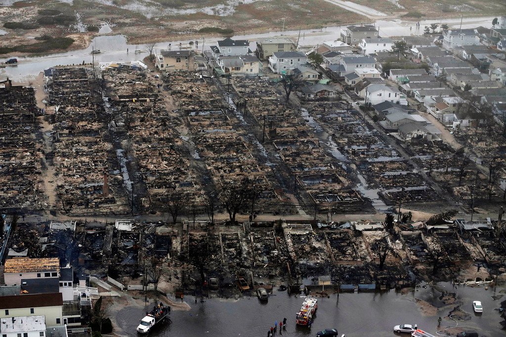 . This Oct. 30, 2012 file aerial photo shows burned-out homes in the Breezy Point section of the Queens borough New York. The tiny beachfront neighborhood told to evacuate before Sandy hit New York burned down as it was inundated by floodwaters, transforming a quaint corner of the Rockaways into a smoke-filled debris field. (AP Photo/Mike Groll, File)