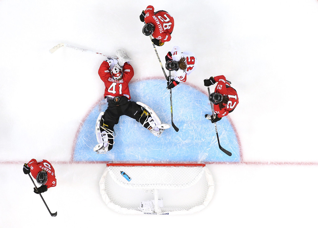 Description of . Florence Schelling #41 of Switzerland falls to the ice in the crease against Jayna Hefford #16 of Canada during the Women's Ice Hockey Playoffs Semifinal game on day ten of the Sochi 2014 Winter Olympics at Shayba Arena on February 17, 2014 in Sochi, Russia.  (Photo by Bruce Bennett/Getty Images)