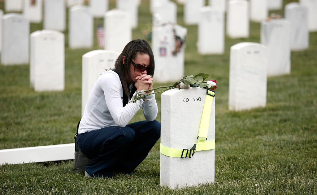 . Afte placing roses atop the headstone, Amy Mixon of Fernandina Beach, Florida, clasps her hands at the grave of her husband Kelly Mixon at Arlington National Cemetery in Virginia May 23, 2013. Mixon made the visit for the Memorial Day weekend to honor her husband who was killed in Afghanistan in 2010.  REUTERS/Kevin Lamarque
