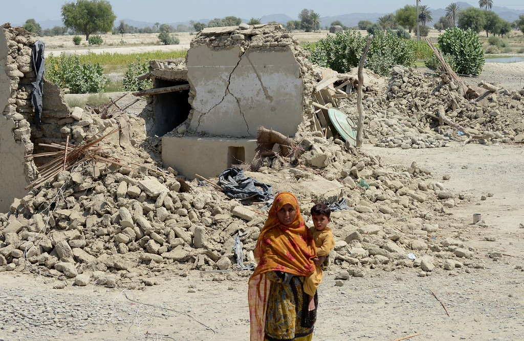 Description of . A Pakistani earthquake survivor holds her child in front of collapsed mud houses at Labach area, in the earthquake-devastated district of Awaran on September 26, 2013.  AFP PHOTO / Banaras KHAN/AFP/Getty Images